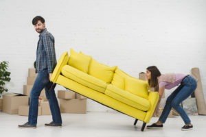 A couple moving furniture
