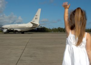 Little girls is looking at an airplane and waving; moving your kids is difficult