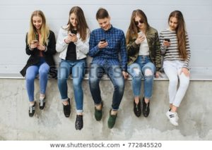 Teenagers sitting side by side and connecting over their phones