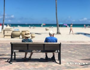Two elderly people are sitting on a bench near the beach, enjoying the sun and the beautiful weather.