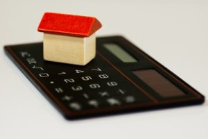 A calculator and a small wooden model house on it.