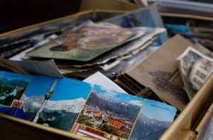A cardboard box full of photos and postcards.