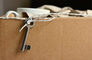 A cardboard box full of stuff with a key hanging out.