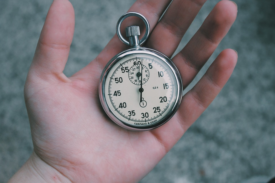 A person holding a stopwatch symbolizing you while thinking about how to speed up your Brooklyn move.