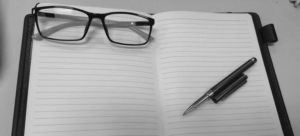 Glasses and a pencil on an open planner.