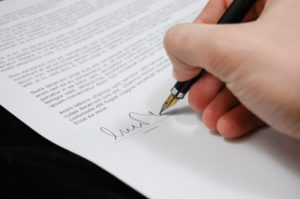 Signing a document when hiring the right moving company in NYC.