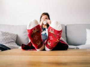 Girl with festive socks lifted her fit on a table, while she is drinking something out of a mug.