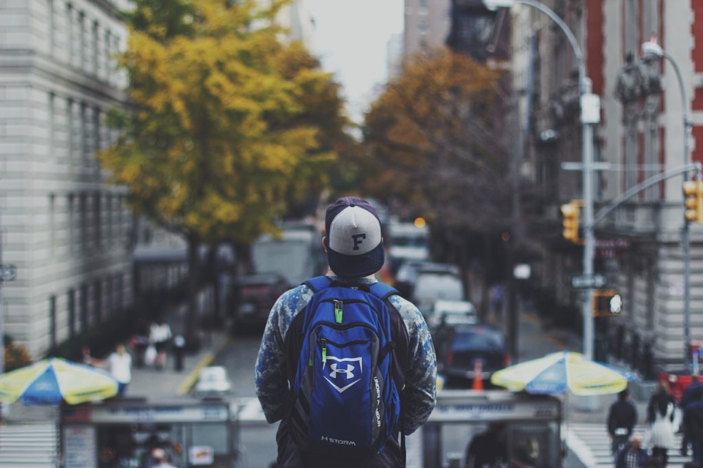 A young man with a backpack symbolizing you when thinking about the places to consider when planning your next move.