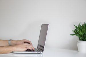 A man typing on a laptop.
