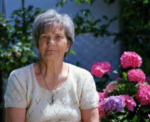 An elderly woman sitting in her garden.