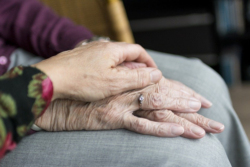 Hand put over two other elderly hands as a sign of support and comfort.