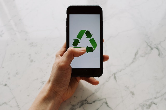 Hand holding a phone with recycle sign.