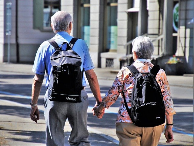 An elderly couple walking hand in hand.