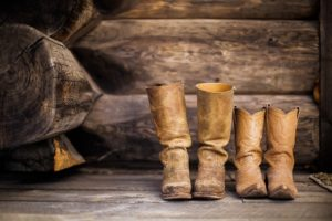 Two pairs of brown leather cowboy boots placed on a wooden deck.