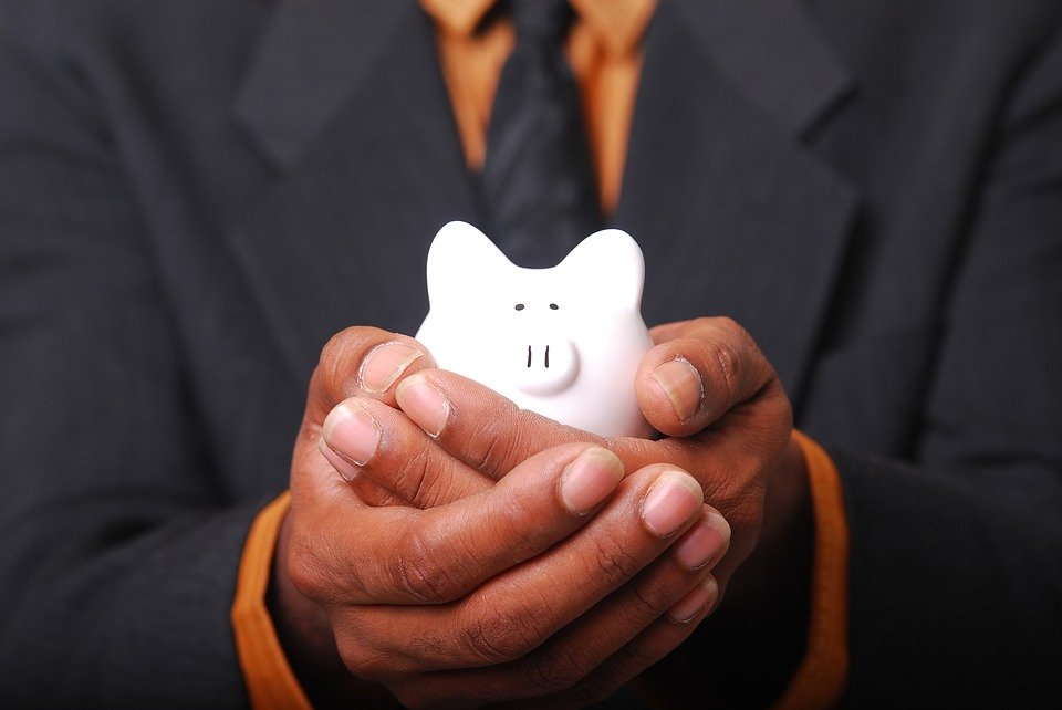 a man in a suit holding a small white piggy-bank.