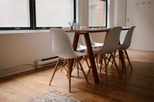 Dinning room with a simple wooden table and white chairs.