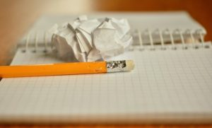 A notebook, a pencil, and a crumpled piece of paper.