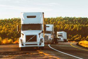 Three trucks on the road.