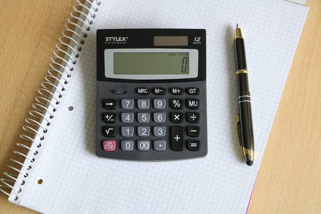 A calculator, notebook, and a pen to use and set the costs when moving in together.