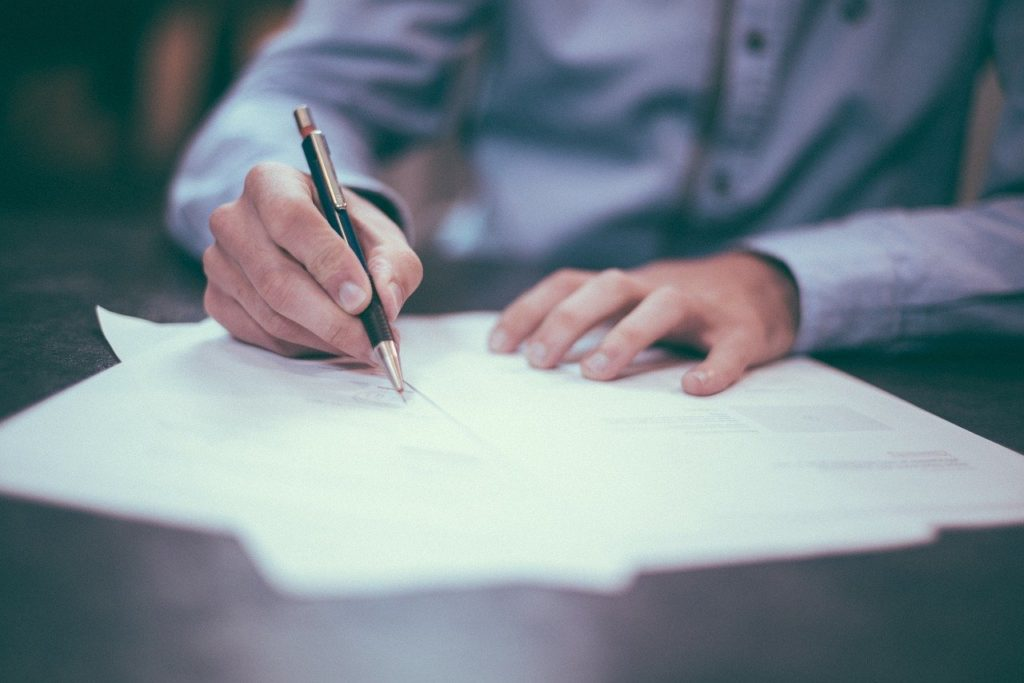 A man signing contracts.