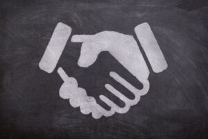 An illustration of a handshake on a black board.