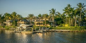 A huge house on the coast in Naples, FL surrounded by numerous palm trees.