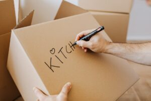A hand writing on a cardboard box.