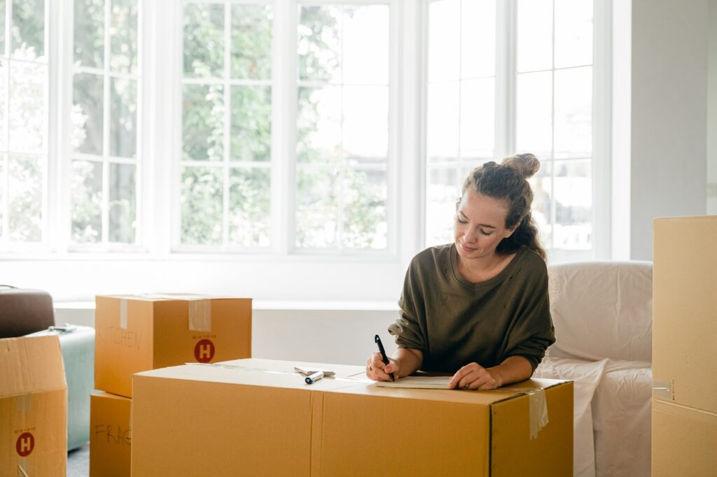 Woman writing on a box organising a long-distance move in New Jersey.