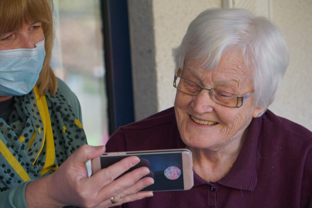A younger woman showing something on a mobile phone to an elderly woman while looking for tips for handling disputes with your landlord.