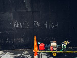 The words rents too high written on a back wall.