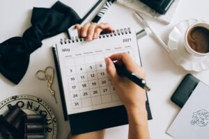 There is a person holding a pen and a calendar.