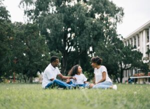 A three-member family is sitting on the grass.