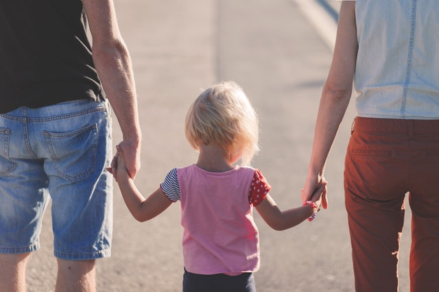 A mother, a father, and a baby are holding their hands.
