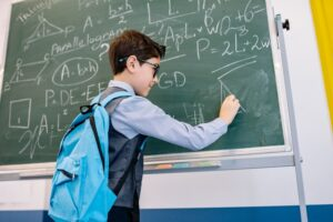A boy is solving a math problem on the green board in one of the great schools in one of the best family-friendly neighborhoods in the New Orleans metropolitan area.