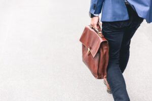 A young professional carrying his man purse on his way to work.