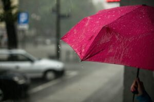 A colorful pink umbrella held by a woman in the rain.